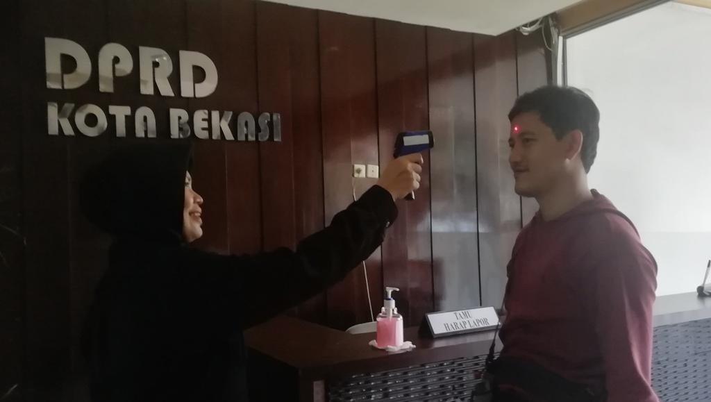 Salah satu Pengunjung DPRD Kota Bekasi melakukan Pengecekan Suhu Tubuh, (17/3).