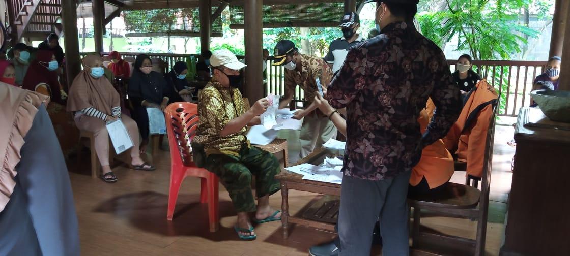 Foto Caption : Warga Terima BST (Bantuan Sosial Tunai) dengan melampirkan persyaratan (Foto Copy KTP dan KK) kepada Petugas, Selasa, (19/1).